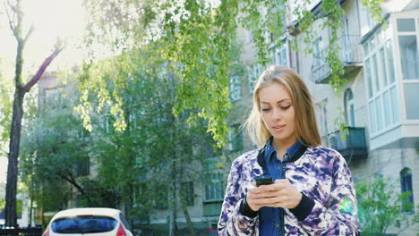 Attractive-Woman-Walking-In-The-City-Enjoys-A-Smartphone-Prores-422-10-Bit