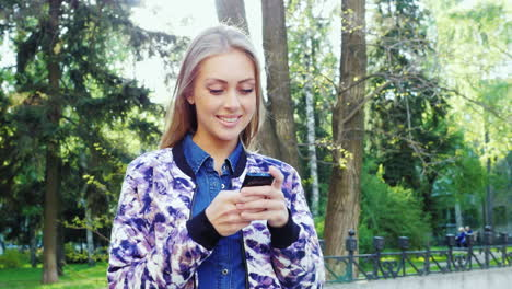 Attractive-Woman-Enjoying-Smart-Phone-In-A-City-Park-The-Sun-Shines-On-It-And-Gives-Beautiful-Reflec