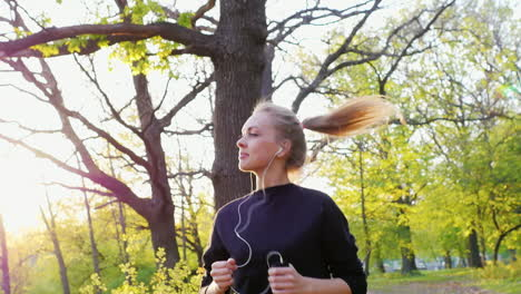 Jogging-In-The-Forest-On-The-Background-Of-The-Setting-Sun-An-Attractive-Woman-Running-In-The-Sun-Sl
