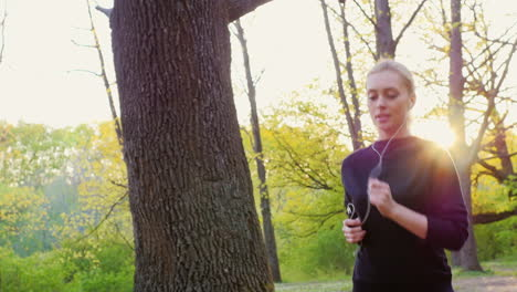 An-Attractive-Young-Woman-Makes-A-Morning-Jog-In-The-Forest-The-Sun-Is-Shining-Beautifully-And-Gives