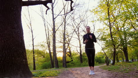 Young-Woman-Jogging-In-The-Forest-The-Sun-Shines-Beautifully-At-The-Camera