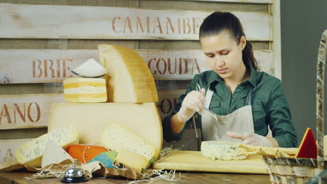 The-Seller-Works-In-A-Shop-Of-Cheeses---Cut-Cheese-With-A-Special-Knife-Made-Of-Wire-Nearby-Are-Larg