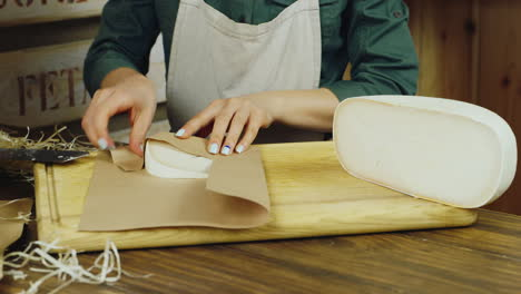Seller-Hands-A-Piece-Of-Cheese-Are-Packed-In-Paper-Packaging-Hd-Video