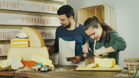 Teamwork---Man-And-Woman-Working-Together-At-The-Counter-Of-The-Cheese-Shop-They-Are-In-A-Good-Mood