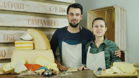 Successful-Small-Business-The-Man-And-The-Woman-Behind-The-Counter-Of-The-Store-Cheeses-Looking-At-C