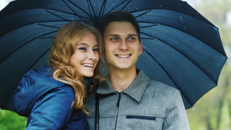 Man-And-Woman-Under-An-Umbrella-The-Rain-Look-Ahead-Laugh-Smile