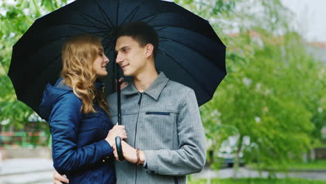 Young-Woman-And-A-Stylish-Man-Standing-On-The-Street-Under-An-Umbrella-It-s-Raining