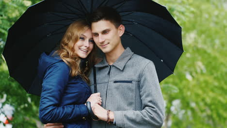 A-Loving-Young-Couple-Under-An-Umbrella-Wait-Out-Rain-Hd-Video