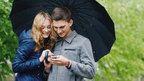 Young-Couple-Enjoys-A-Smartphone---Standing-Under-An-Umbrella-The-Rain-Connected-In-Any-Weather-Hd-V