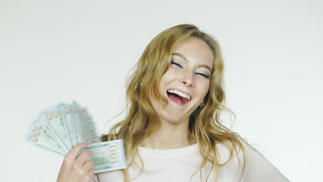 Young-Woman-Counting-Money-Rejoices-Shot-On-A-White-Background-In-The-Studio