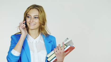 Woman-With-A-Stack-Of-Books-Speaks-On-The-Phone-Hd-Video