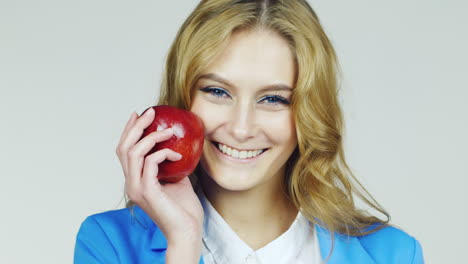 Attractive-Blue-Eyed-Woman-With-Red-Apple-Filmed-At-Studio-On-A-White-Background
