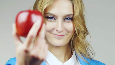 Portrait-Of-Attractive-Blue-Eyed-Woman-With-Red-Apple-Focus-Switches-Smoothly-From-The-Face-On-The-A