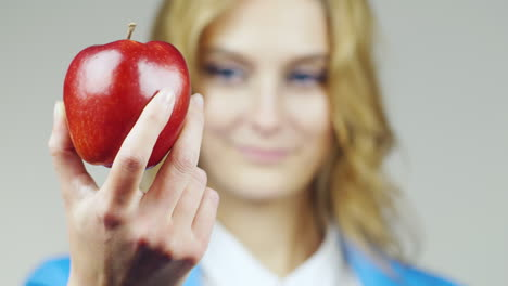 Close-Up-Of-A-Blue-Eyed-Woman-With-Red-Apple-Hd-Video