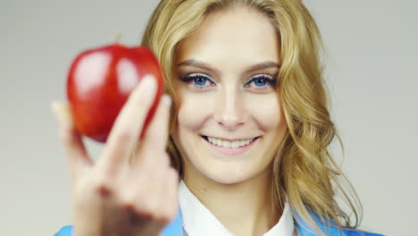 Portrait-Of-Attractive-Blue-Eyed-Woman-Holds-Up-A-Red-Apple-Hd-Video