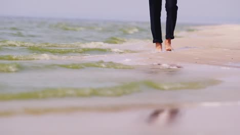 A-Barefooted-Man-In-Trousers-Walks-Along-The-Seashore-Water-Washes-His-Feet-Dream-Of-Vacation-Concep