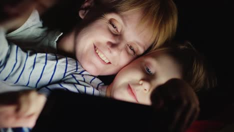 Mother-And-Daughter-Enjoy-The-Tablet-Lie-In-Bed-At-Night