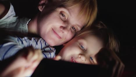 Happy-Mother-With-Her-Daughter-Together-I-Play-On-The-Tablet-Lie-Side-By-Side-Face-To-Face-In-Bed