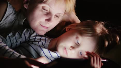 Mom-And-Daughter-Are-Lying-On-The-Bed-Together-Looking-At-The-Screen-Of-The-Tablet-In-The-Dark-The-S