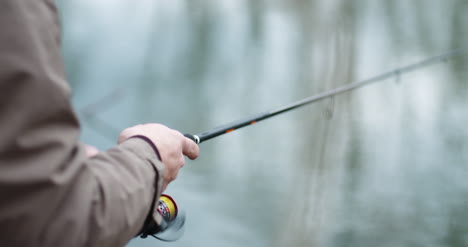 Fisherman-Holding-Fishing-Rod-In-Hands-4