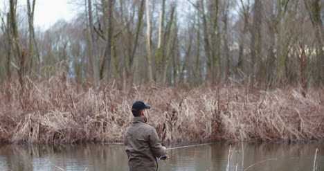Man-Fishing-At-Lakeshore-In-Forest-5