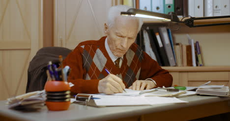 Senior-Businessman-Writing-On-Paper-At-Table-In-Office-6