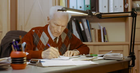 Senior-Businessman-Writing-On-Paper-At-Table-In-Office-7
