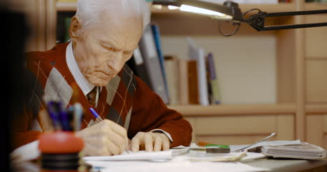 Senior-Businessman-Writing-On-Paper-At-Table-In-Office-8