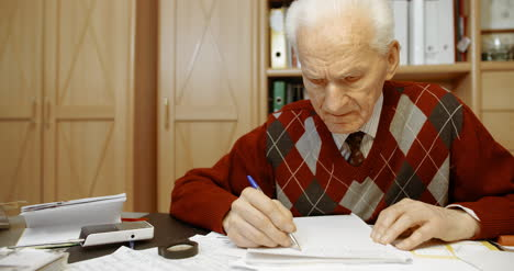 Senior-Businessman-Writing-On-Paper-At-Table-In-Office-16