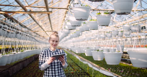 Gardener-Using-Digital-Tablet-At-Greenhouse-And-Smile-2