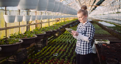 Gardener-Using-Digital-Tablet-At-Greenhouse-And-Smile-4