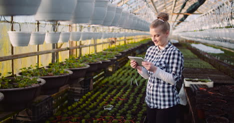 Gardener-Using-Digital-Tablet-At-Greenhouse-And-Smile-5