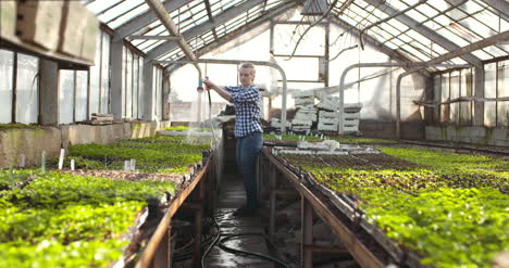 Female-Farmer-Watering-Plants-In-Greenhouse-Agriculture