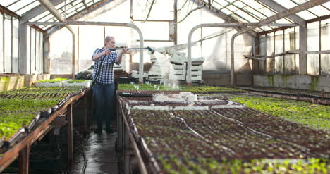 Female-Farmer-Watering-Plants-In-Greenhouse-Agriculture-2