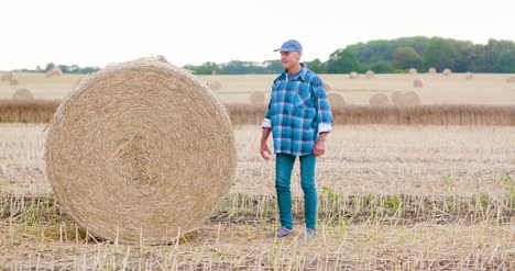 Smiling-Farmer-Rolling-Hay-Bale-And-Gesturing-In-Farm-1
