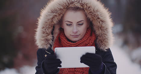 Female-Tourist-Using-Digital-Tablet-In-Forest-In-Winter-2