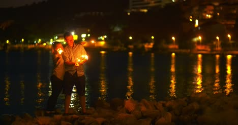 Couple-Holding-Sparklers-At-Seashore-1