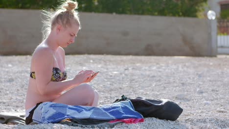 Young-Lady-Sitting-On-Beach-While-Using-Her-Mobile-Device-1