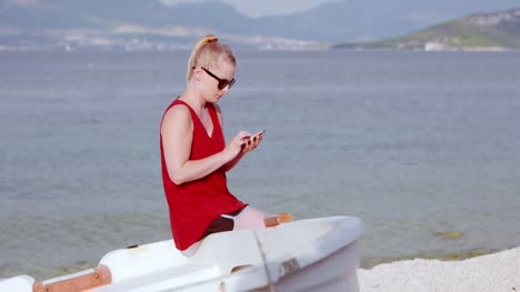 Young-Lady-Sitting-On-Beach-While-Using-Her-Mobile-Device-10