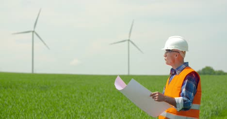 Engineer-Analyzing-Plan-While-Looking-At-Windmills-In-Farm