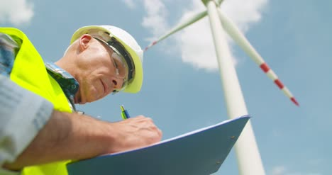 Engineer-Writing-On-Clipboard-While-Doing-Wind-Turbine-Inspection