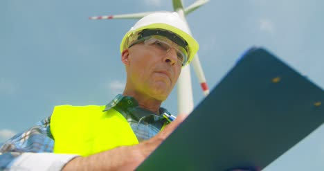 Engineer-Writing-On-Clipboard-While-Standing-Against-Windmill-1