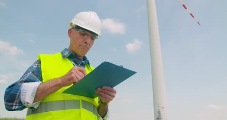 Engineer-Writing-On-Clipboard-While-Standing-Against-Windmill-2