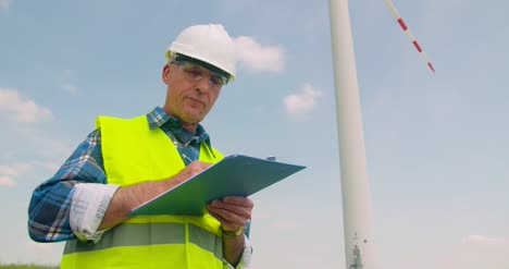 Engineer-Writing-On-Clipboard-While-Standing-Against-Windmill-3