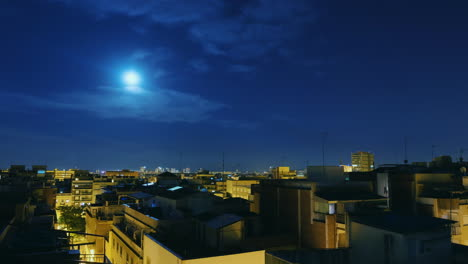 Moonrise-Over-The-City-And-The-Roofs-Of-Houses-Timelapse-From-Evening-To-Dawn-The-Sun-Rises-Over-The