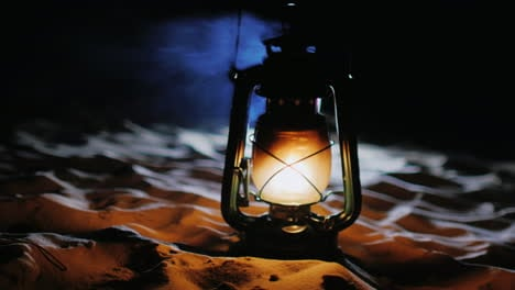 Vintage-Oil-Lamp-Standing-On-The-Sand-Shines-In-The-Dark-Prores-422-10-Bit-Video