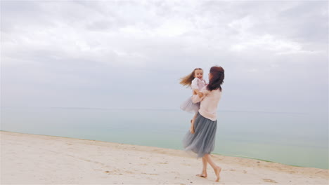 Cheerful-And-Carefree-Mother-Playing-With-Her-Daughter-On-The-Beach