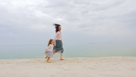 Mom-And-Daughter-Having-Fun-Running-Around-On-The-Beach-Happy-Childhood