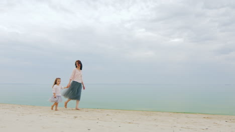 Mother-And-Daughter-Walking-Slowly-Along-The-Seashore