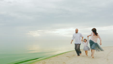 Family-Fun-Mom-Dad-And-Daughter-Run-On-The-Beach